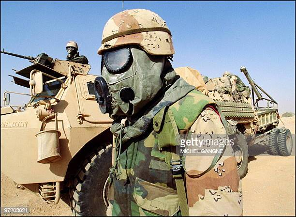 A US soldier stands 09 February 1991 somewhere in Saudi Arabian desert in front of a French armored vehicle from the 6th Foreign Legion Engineers...
