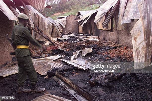 A soldier stands 19 March 2000 amid burned remains of up to 250 Ugandans of Movement for the Restoration of the Ten Commandments of God that...
