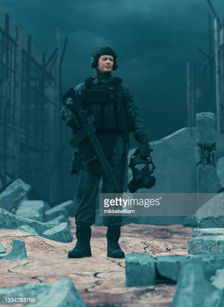 soldier stands alone in a warzone with weapons and protective face mask - task force stock pictures, royalty-free photos & images