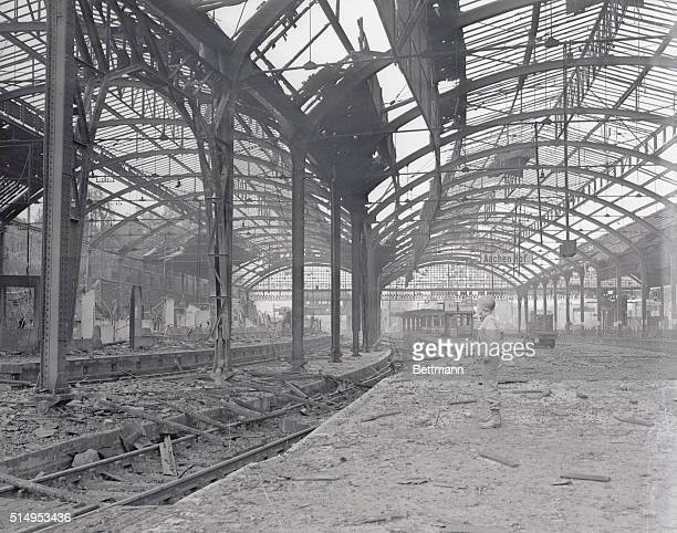 A US soldier stands amid the ruins of railway station at AAchen typifying the desolation left in the wake of the German forces who were driven out of...