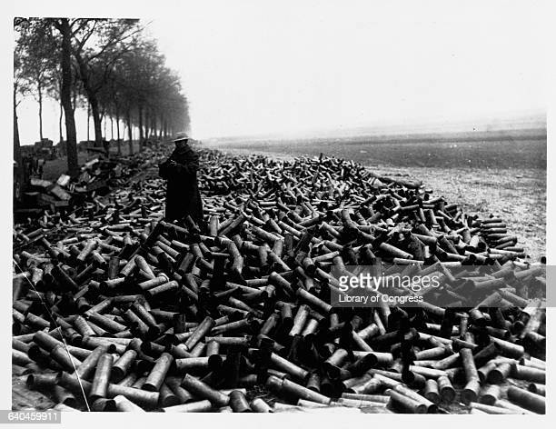 Soldier stands among a massive pile of artillery shell casings, the remains of what was fired into the German lines.