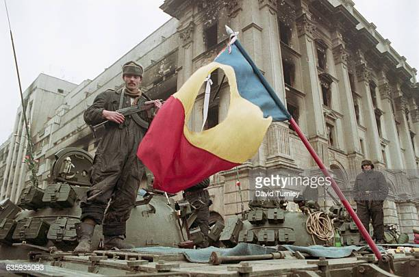 A soldier stands atop a tank with a rifle in Bucharest's Revolution Square after the overthrow of Romanian president Nicolae Ceausescu In front of...