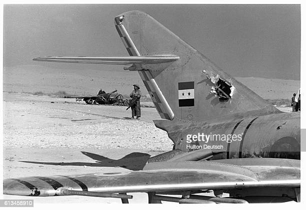 A soldier stands behind a burnt out Egyptian aircraft at Al Arish airport | Location Al Arish Egypt