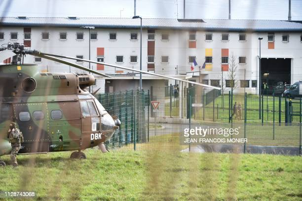 A soldier stands beside an army helicopter in front of the Penitentiary center of Alencon in CondesurSarthe western France on March 5 where a...
