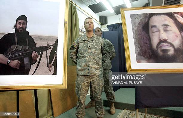 A US soldier stands between two images of alQaeda leader in Iraq Abu Musab alZarqawi during a US military briefing 08 June 2006 in Baghdad The image...