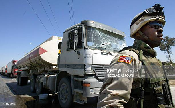 US soldier stands close to an oil tanker that was hit by a roadside bomb 01 April 2004 in northwest Baghdad The charge went off as a US army convoy...