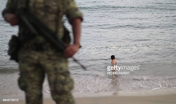 A soldier stands guard as a girl stands on the shore of a beach in a touristic area of Acapulco in the Mexican state of Guerrero on October 27 2015...