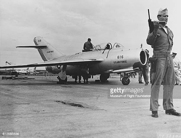 A soldier stands guard as a U S Air Force ground crew gives a Russianbuilt MIG15 fighter a final check in preparation for the first test flight on...