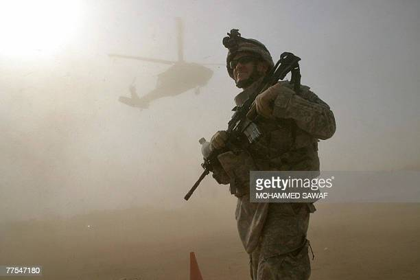 Soldier stands guard as Blackhawk helicopter lands at a field in the holy city of Karbala during a hand over ceremony, 29 October 2007. The US...