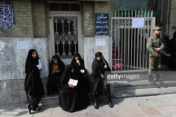 A soldier stands guard as Iranians line up in long lines to vote in key elections for Parliament and the Assembly of Experts in Tehran Iran on...