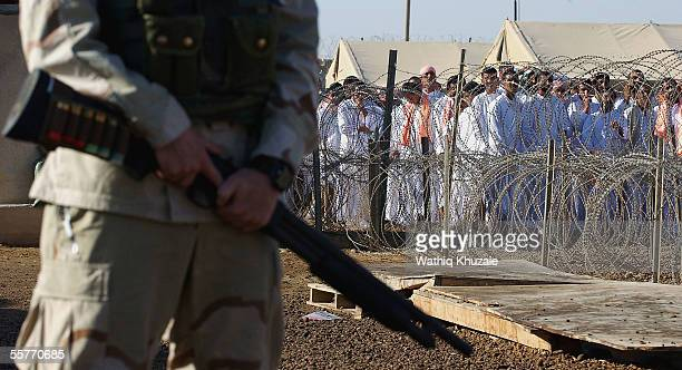 S soldier stands guard as Iraqi detainees stand in line waiting to be processed for release from Abu Ghraib prison facility on September 26 2005 in...