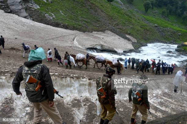 CRPF soldier stands guard as the first batch of the pilgrims leaving towards to the Holy Cave from Nunwani base camp of Pahalgam during the first...