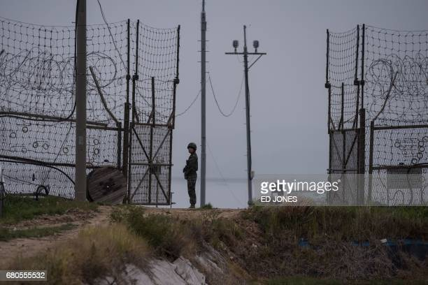 A soldier stands guard at an opening to the fence of the Demilitarized Zone during maintenance on Gyodong a tiny outlying island near to the west of...