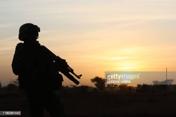 Soldier stands guard at sunset as France's President and Niger's President Mahamadou Issoufou take part in a military ceremony at the Martyr Quarter...