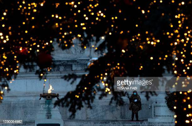 Soldier stands guard by the Altare della Patria monument to late King Vittorio Emanuele II, and the municipality's Christmas tree set up on Piazza...