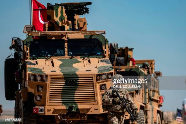 US soldier stands guard during a joint patrol with Turkish troops in the Syrian village of alHashisha on the outskirts of Tal Abyad town along the...