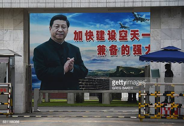 A soldier stands guard in front of a huge portrait of Chinese President Xi Jinping at the entrance to a military base in Guilin in China's southern...