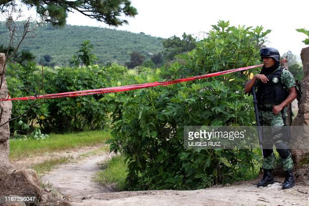 Soldier stands guard in the area where forensic experts are working using an excavator to dig in an old 30-meter well turned into into a mass grave...
