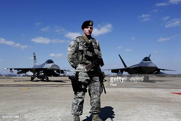 S soldier stands guard near a US F22 stealth fighter at the Osan Air Base on February 17 2016 in Pyeongtaek South Korea US military has deployed four...