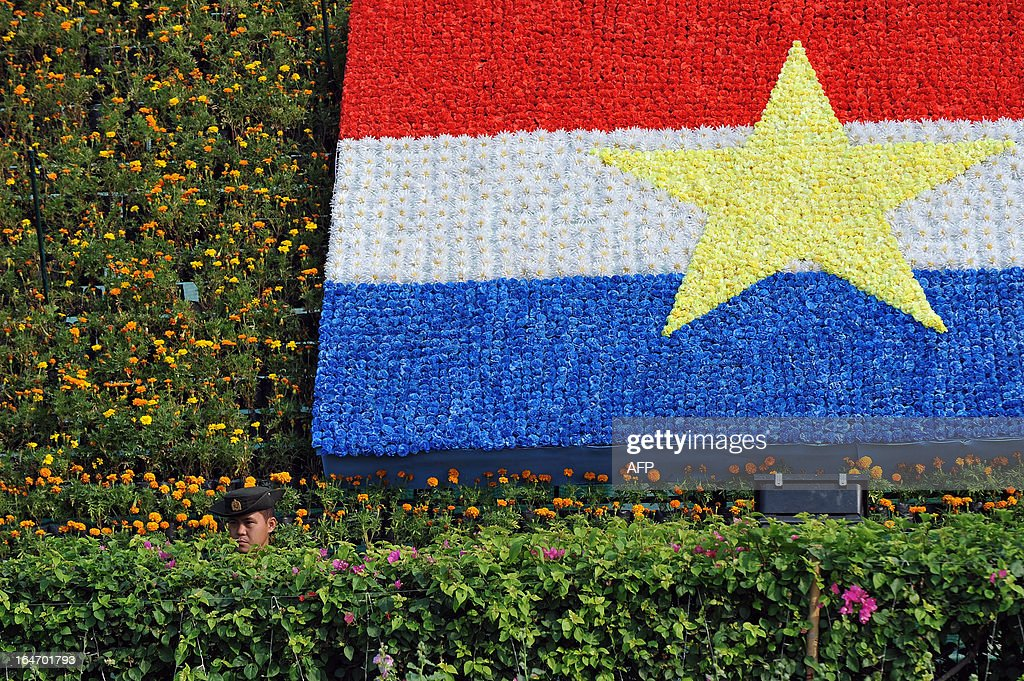 A soldier stands guard next to a flag made of flowers during a ceremony marking Myanmar's 68th Armed Forces Day at a parade ground in Naypyidaw on March 27, 2013. Opposition leader Aung San Suu Kyi attended Myanmar's Armed Forces Day for the first time. AFP PHOTO / Ye Aung THU