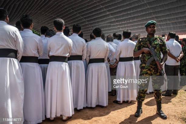 A soldier stands guard next to members of the clergy during a mass funeral at St Sebastian's Church on April 23 2019 in Negombo Sri Lanka At least...