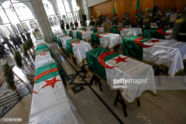 Soldier stands guard next to the national flag-draped coffins containing the remains of 24 Algerian resistance fighters decapitated during the French...