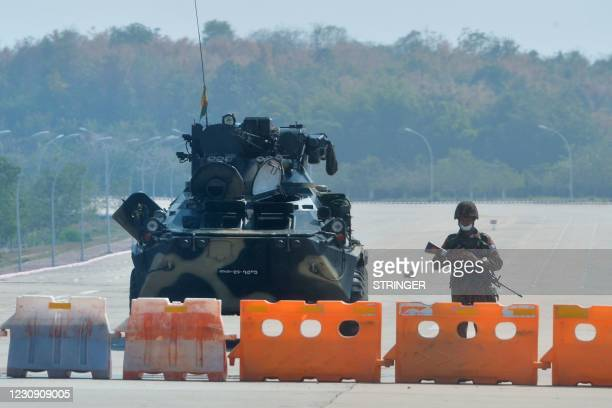 Soldier stands guard on a blockaded road to Myanmar's parliament in Naypyidaw on February 1 after the military detained the country's de facto leader...