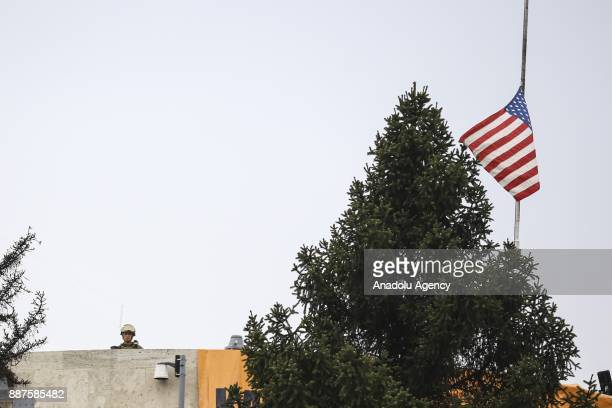 Soldier stands guard on the roof as members of the Confederation of Public Servants Trade Unions stage a protest in front of U.S. Embassy in Ankara,...