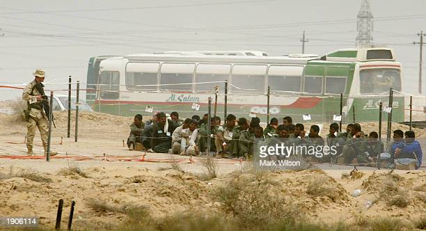 A soldier stands guard over Iraqi prisoners of war at Camp Bucca April 8 2003 near Umm Qasr Iraq The Enemy Prisoner of War camp is currenty holding...