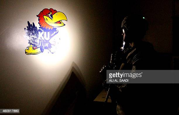 US soldier stands in front of a logo of the Kansas Jayhawks basketball team painted on a wall at the Taji base complex which hosts Iraqi and US...