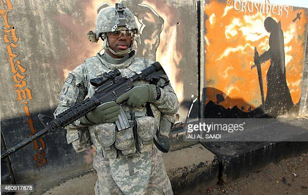 US soldier stands in front of graffiti painted on concrete blast walls at the Taji base complex which hosts Iraqi and US troops and is located thirty...