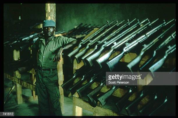 UNITA soldier stands in front of weapons captured from government troops January 23 1990 in Likwa Angola The National Union for the Total...