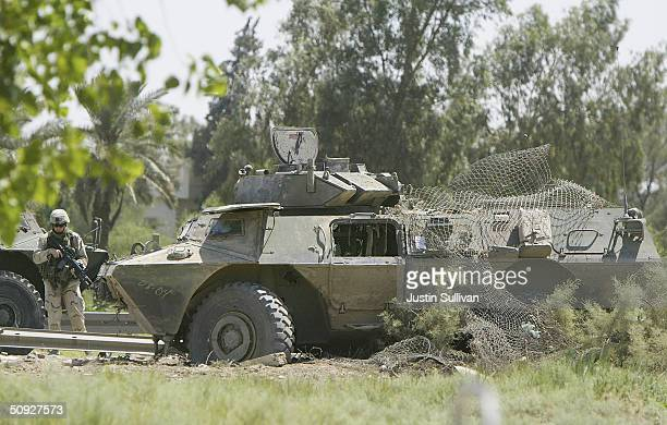 S soldier stands near a Striker armored vehicle that was hit by a roadside attack June 5 2004 in Baghdad Iraq One soldier was killed and three more...