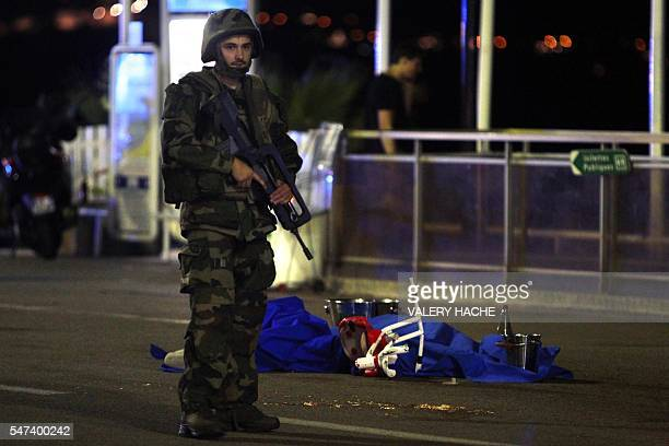 A soldier stands next to a dead body covered with a blue sheet on the Promenade des Anglais seafront in the French Riviera town of Nice on July 15...