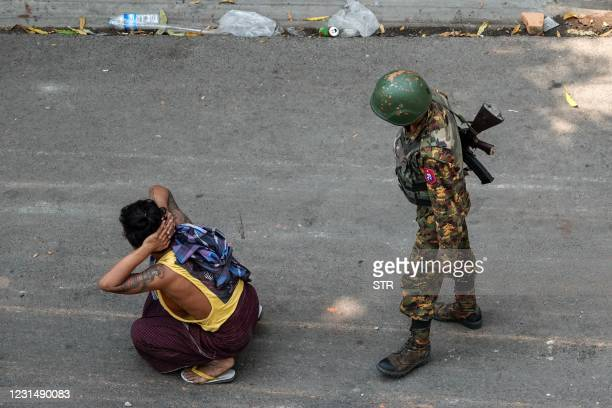 Soldier stands next to a detained man during a demonstration against the military coup in Mandalay on March 3, 2021.
