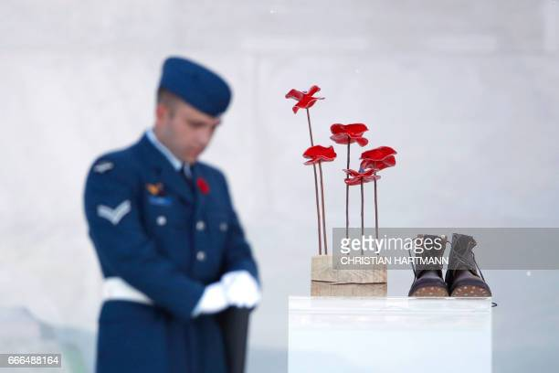 A soldier stands next to a sculpture of red poppies by artist Bernard Freseau and boots dropped off the entrance of the Canadian National Vimy...