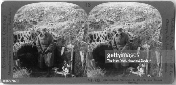 A soldier stands next to camouflaged trenches in the Chemin des Dames Sector France WWI