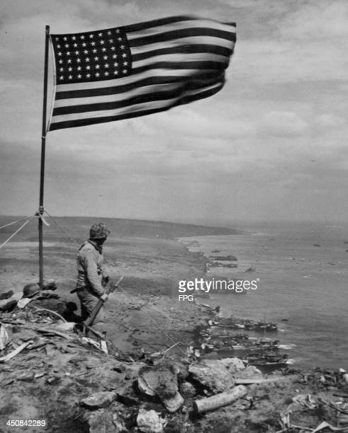 A US soldier stands next to the American flag marking the allied victory at Iwo Jima during World War Two Japan March 1945