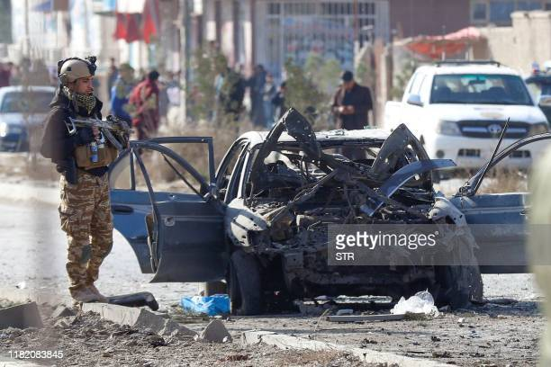 A soldier stands next to the site of a suicide attack in Kabul on November 13 2019 At least seven people were killed and seven wounded when a car...
