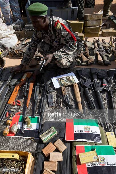 Soldier stands next to weapons and ammunitions seized from Islamist fighters exhibited with flags from the United Arab Emirates by the Malian army in...