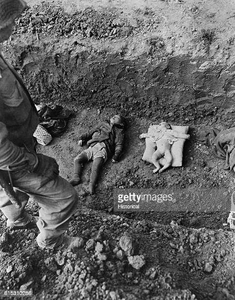 A soldier stands over a baby and a child lying dead in a shallow grave They were murdered at a Nazi concentration camp