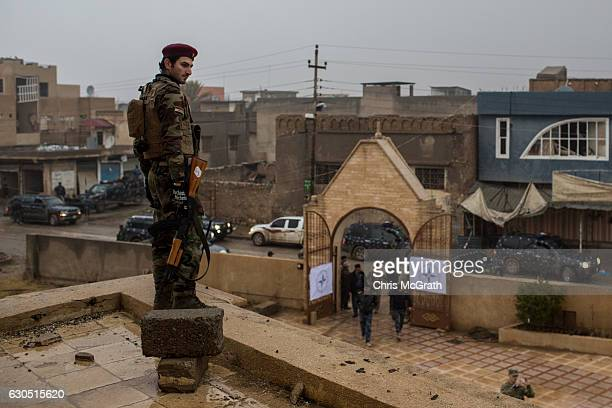 A soldier stands watch on the rooftop as people arrive for the Christmas Day mass at Mar Hanna church in Qaraqosh on December 25 2016 in Mosul Iraq...