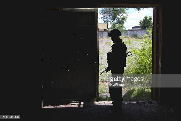 Soldier stays in front of the drilled with bullets garage door after the clash with prorussian terrorists at a check point near Slaviansk Ukrainian...