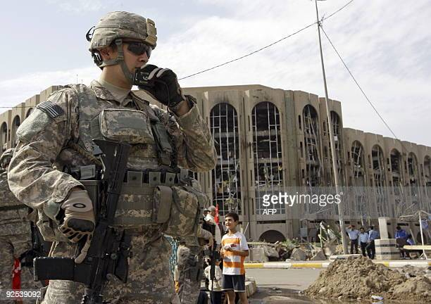 A US soldier surveys the area of the destroyed Justice Ministry in central Baghdad on October 30 five days following a suicide bus bombing outside US...
