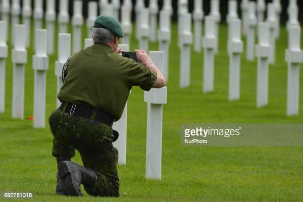 Soldier takes a picture of the graves of fallen soldiers at the Normandy American Cemetery that contains the remains of 9,387 American military dead,...