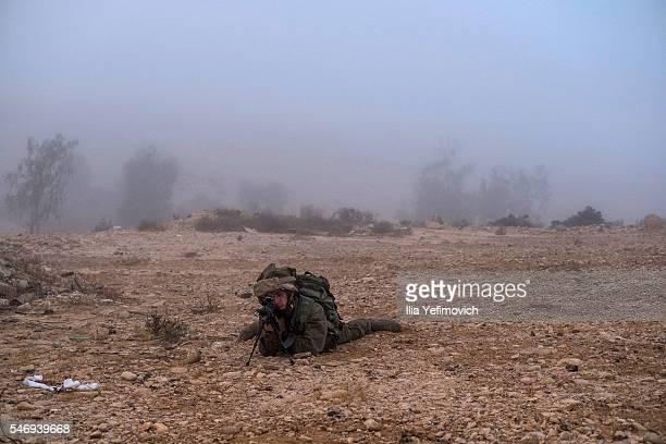 A soldier takes aim as Israeli male and female combat soldiers of the Bardales battalion take part in a long day of practise in a heavy fog on July...