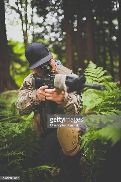 A soldier takes aim with his gun.