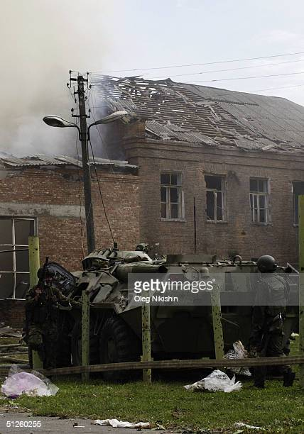 A soldier takes cover as special forces storm a school seized by Chechen separatists on September 3 2004 in the town of Beslan Russia Russian...