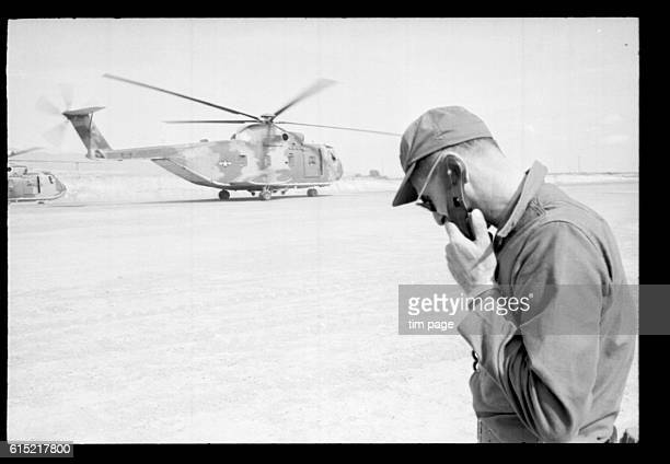 A soldier takes instruction by radio on the airfield at Quang Ngai during the aerial evacuation of the An Lao Valley Vietnam 1965