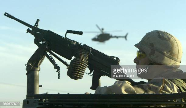 A US soldier takes position during clashes in Baghdad's western suburb of Abu Gharib 31 October 2003 Four Iraqis including a policeman were killed...